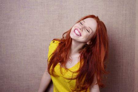 Single beautiful young red haired woman in yellow shirt wearing big showy grin over simple brown cloth background with copy space