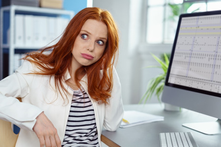 Single insecure beautiful woman with long red hair waiting at desk with computer as if she is having technical problems or waiting for help