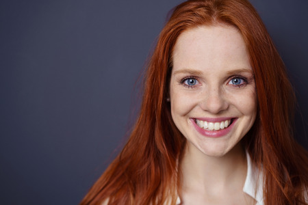 Close up on face of pretty smiling young adult woman in long red hair and blue eyes with copy space over black background