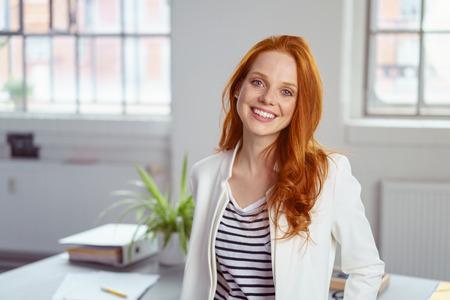 Stijlvolle aantrekkelijke jonge roodharige zakenvrouw met een mooie glimlach staan voor een tafel in het kantoor grijnzen op de camera