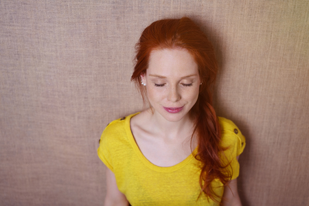 Single gorgeous young red haired woman in yellow shirt with eyes closed and slight grin as if to dream over simple brown canvas background with copy space Stock Photo