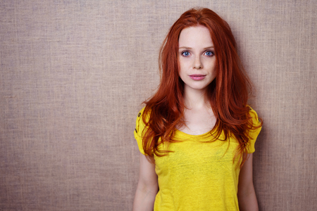 Calm faced single gorgeous young red haired woman in yellow shirt over simple brown cloth background with copy space 版權商用圖片 - 61147148