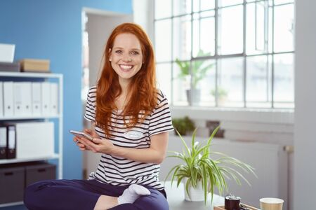 Vivacious young businesswoman sitting in the lotus position on a desk in the office holding her mobile phone and grinning at the camera