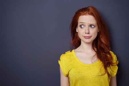 Single gorgeous young long haired woman in yellow shirt with puzzled or worried expression over simple dark background with copy space Stock Photo