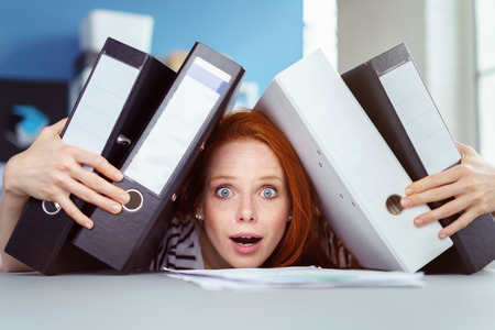 leaning forward: Stressed businesswoman leaning forward crushed by the weight under a pile of binders in a spoof on overwork and pressure