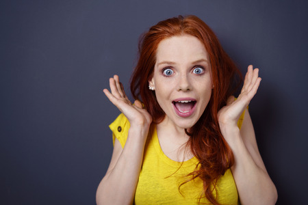 Attractive young woman with a look of wide eyed amazement holding her hands to the sides of her head with her mouth open