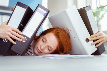 work load: Young businesswoman napping under a pile of binders which she is clasping in her arms overwhelmed by the work load