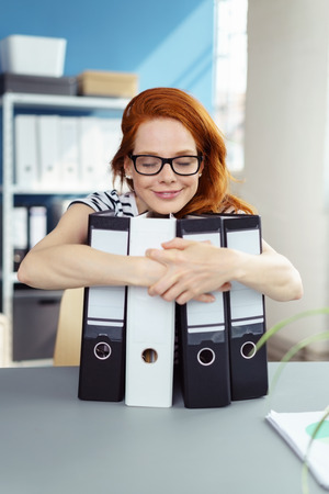 short sleeved: Cute smiling red haired woman in short sleeved shirt with closed eyes and contented expression hugging four large note paper binders on desk in office