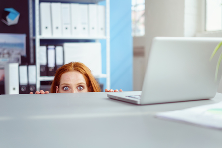 Young businesswoman peering over her desk in the office in wide eyed horror or amazement with just her eyes visible