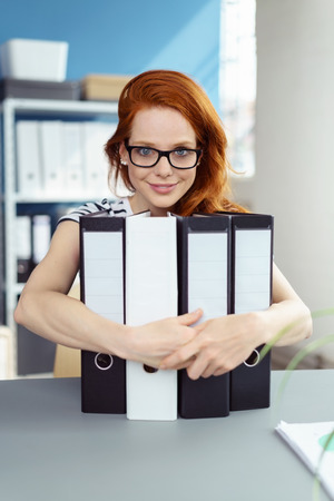 Happy contented young redhead businesswoman wearing eyeglasses sitting at a table in the office clutching binders and smiling Stock Photo