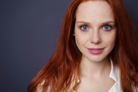 Close up on face of beautiful young adult grinning woman in long red hair and blue eyes with copy space over black background Stock Photo