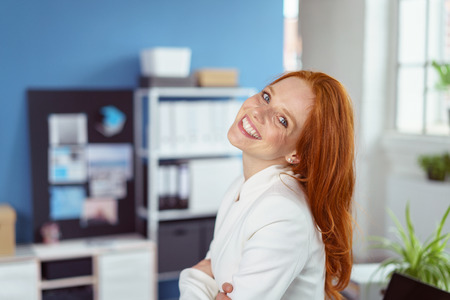 head tilted: Friendly confident businesswoman standing with folded arms in the office looking at the camera with her head tilted back and a charming smile