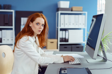 puckered lips: Beautiful young woman in long red hair and white blazer jacket with puckered lips typing on computer in small office with shelf and blue wall in background Stock Photo
