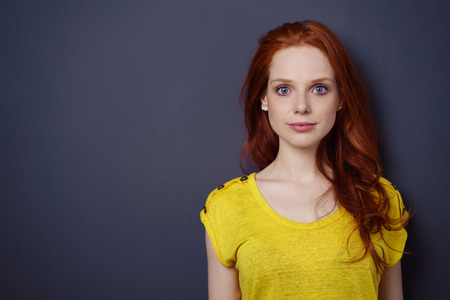confident woman: Single gorgeous young red haired woman in yellow shirt with calm or relaxed expression over simple dark background with copy space on side
