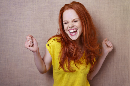Single gorgeous young red haired woman in yellow shirt dancing or rejoicing about something over simple brown cloth background with copy space