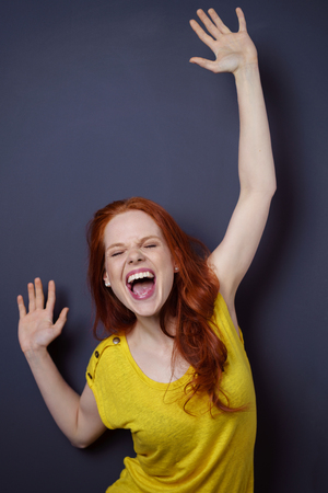 wonder: Single gorgeous young long haired woman in yellow short sleeve shirt reaching arms up as if to celebrate or laugh over dark background with copy space