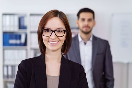 A businesswoman with a confident smile wearing glasses standing in the foreground in front of a male colleague in the office, head and shoulders