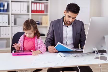 Junge Unternehmer Babysitter seine kleine Tochter im Büro, während sie sitzt neben ihm auf einem playstation arbeiten, wie er Papierkram tut