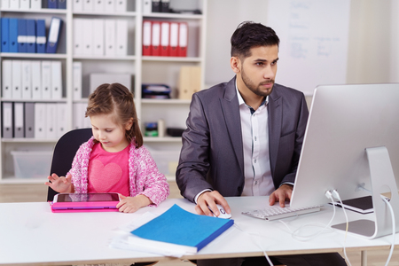 Young businessman babysitting his daughter in the office as she sits alongside him as he works on his computer 스톡 콘텐츠
