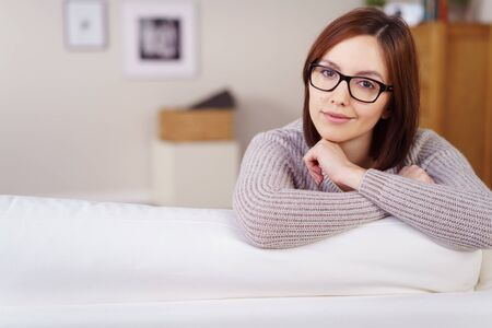 wry: Charismatic attractive young woman wearing glasses giving a wry smile as she leans over the back of a sofa looking at the camera