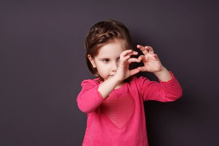fingers on top: Adorable small girl in a colorful pink top making a heart gesture with her fingers to show her love for her parents on a dark background