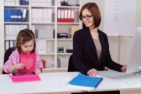 Junge Unternehmerin Babysitter im Büro als ihre niedliche kleine Tochter spielt auf einem Spielzeug-Tablette neben ihr, als sie funktioniert