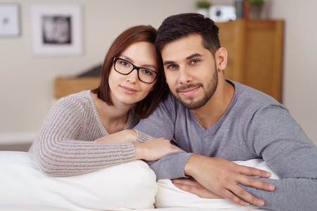 Affectionate young couple posing arm in arm smiling at the camera as they sit together on a sofa leaning on the back looking at the camera Stock Photo