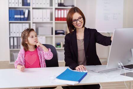 Junge Unternehmerin ihre kleine Tochter amüsant, als sie ihr im Büro lächelnd, als sie zeigt ihr etwas auf dem Computer-Bildschirm babysits