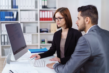 Young business partnership of an attractive stylish man and woman sitting together at a desktop computer in a serious meeting reading the screen