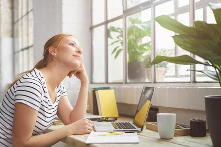 Une jeune femme assise en train de rêver avec son bureau, se penchant le menton sur sa main et regardant la fenêtre à côté avec un sourire de rêve de plaisir Banque d'images - 61147244