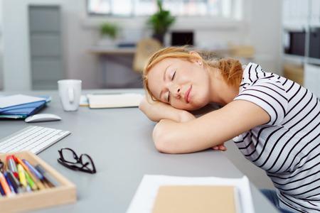 cansancio: Atractiva joven diseñador dormir en el trabajo, con la cabeza apoyada sobre sus manos sobre el escritorio y una expresión pacífica
