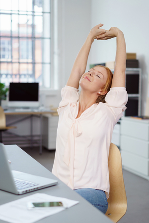 Contented attractive young businesswoman stretching in her chair in the office with her arms raised and eyes closed to relax