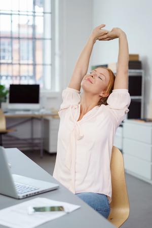 Contented jeune femme d'affaires attrayant étirement dans sa chaise dans le bureau avec ses bras levés et les yeux fermés pour se détendre Banque d'images - 64865916