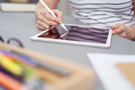 using tablet: Young female designer or illustrator working with a stylus and tablet, close up of her hands and the device