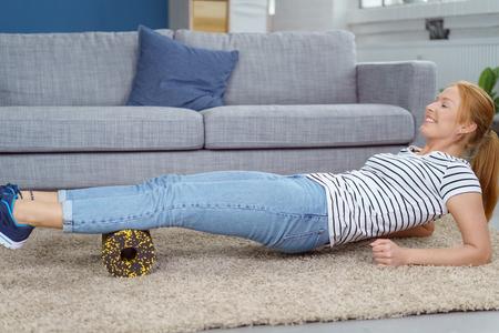 mujer sola: Sola mujer joven en cola de caballo, camisa a rayas y pantalones vaqueros que usan espuma aparato de masaje rollo en el piso de la sala de estar para trabajar en músculos de la pantorrilla