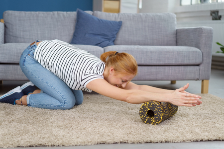 Young woman in striped shirt and jeans massaging forearms with foam roll while stretching spinal areas of back Stock Photo