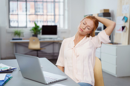 relieve: Young business woman relaxing her neck and shoulders to relieve stress at the office tilting her head to one side with her eyes closed