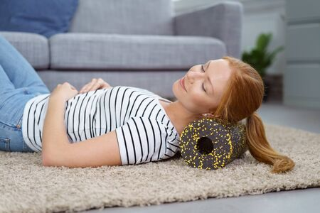 red haired: Contented young red haired woman in pony tail, striped shirt and jeans resting back of head and neck on foam roll massage device on living room floor in front of sofa Stock Photo