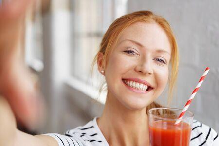 tomando refresco: Mujer joven feliz con una sonrisa vivaz celebración de un jugo de verduras recién licuado saludable en su mano en un concepto de dieta de bienestar y sano