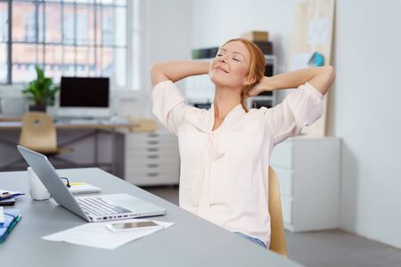 Happy relaxed successful businesswoman taking a break in the office sitting back with her hands behind her head and eyes closed
