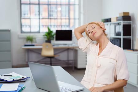 休憩を取り、彼女の目でリラックスする瞬間疲れの若い実業家が閉じられ、頭側に傾いて