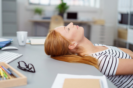 Exhausted young woman taking a break at the office lying back with her head resting on her desk and eyes closed , close up profile view Stock Photo