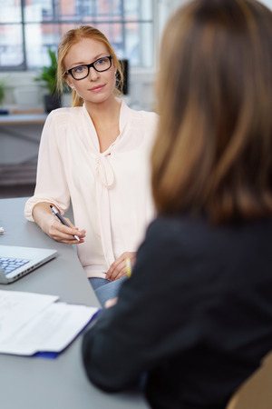 Two female business colleagues in a meeting sitting at a table in the office having a serious discussion Stock Photo