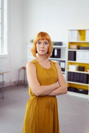 authoritative: Serious authoritative young businesswoman standing in the office with folded arms looking at the camera
