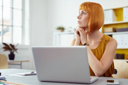 business planning: Businesswoman sitting at her desk in the office with a laptop pondering over a problem looking away to the side with a thoughtful expression Stock Photo