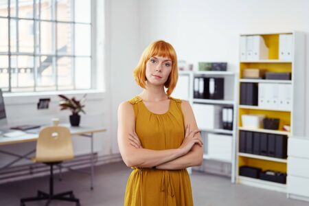quizzical: Confident young businesswoman with a quizzical expression standing with folded arms in the office looking at the camera with her head tilted to the side