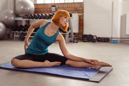 tänzerin: Fit attraktiv barfuß junge Frau arbeitet in einem Fitness-Studio eine anmutige Pose auf einer Yoga-Matte, die zeigt, ihre Geschmeidigkeit