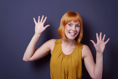 splayed: Mischievous young redhead woman grinning at the camera with her hands raised splayed open, upper body on blue