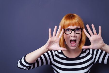 Playful young woman wearing glasses leaning forward shouting at the camera with both hands splayed open in front of her