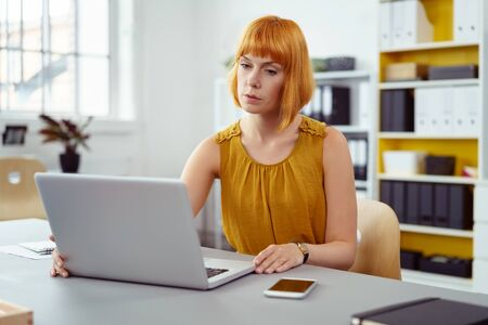 head tilted: Dedicated young businesswoman working at a laptop computer as she sits at a table in the office reading the screen with a thoughtful expression and head tilted Stock Photo
